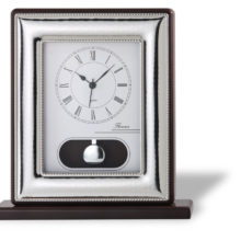 Clock with pendulum on silver and wooden base.